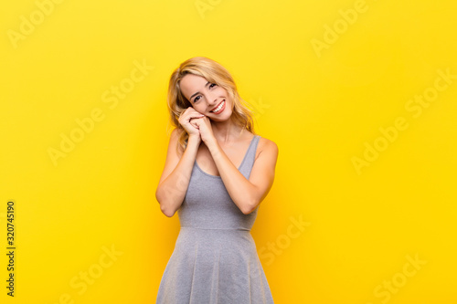 young blonde woman feeling in love and looking cute, adorable and happy, smiling Canvas Print
