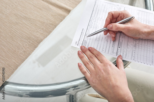 Fototapeta Hands of young female social worker with pen over paper helping her client with filling in health insurance claim form obraz