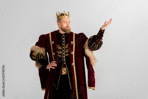 Fotografía king with crown pointing with hand isolated on grey