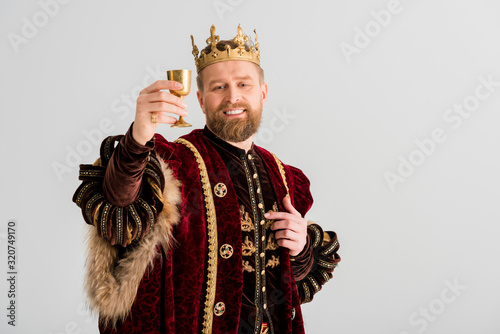 Fotografie, Obraz smiling king with crown holding cup isolated on grey