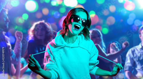 nightlife-entertainment-and-people-concept-happy-young-woman-in-black-sunglasses-wearing-hoodie-at-nightclub-over-lights-background