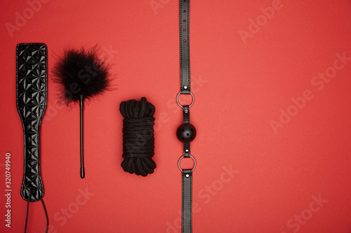 Fototapeta top view of black paddle, gag, rope, feather tickler isolated on red obraz