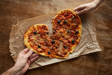 Cropped View Of Couple Holding Delicious Italian Pizza In Broken Heart Shape On Baking Paper At Wooden Table