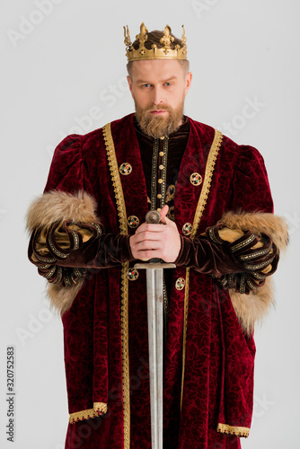 Foto serious king with crown holding sword isolated on grey