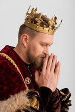 Side View Of King With Crown Praying Isolated On Grey
