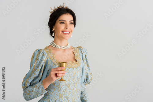 smiling queen with crown holding cup isolated on grey