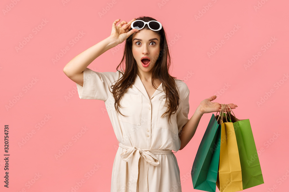 Fototapeta Lets go shopping. Amused and excited female shoppaholic having fun browsing through city malls, holding shop bags, taking-off glasses seeing exactly what been looking for, pink background