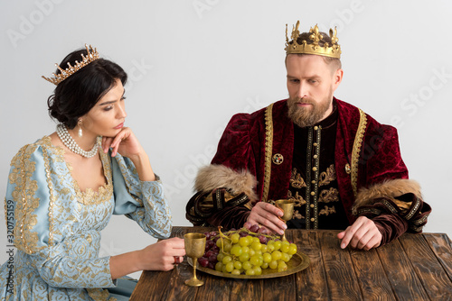 thoughtful queen and king with crowns sitting at table isolated on grey