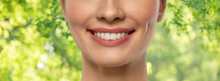 Beauty, Dental Care And Teeth Whitening Concept - Close Up Of Beautiful Young Woman With White Smile Over Green Natural Background