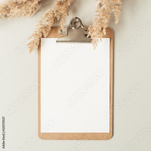 Obraz Flat lay minimalist home office desk with blank sheet clipboard with copy space for text, reeds branch, casket on neutral background. Top view work, business, education template. - fototapety do salonu