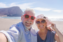 Couple Of Seniors Travelling And Taking A Selfie In A Beautiful Beach With A Mountain At The Background - Smiling And Ejoying Looking At The Camera Wearing Sun Glasses - Vacations Lifestyle