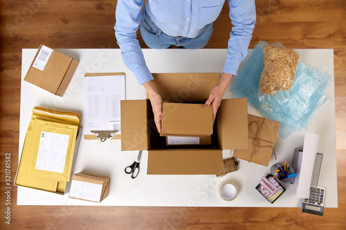 delivery, mail service, people and shipment concept - close up of woman packing fragile parcel boxes at post office - 320761582