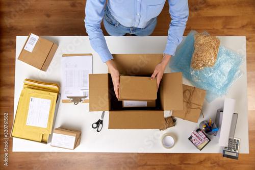 dostawa, poczta, ludzie i pojęcie wysyłki - zamyka up kobieta pakuje delikatnych paczek pudełka na poczcie