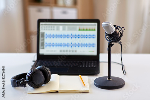 Photo post production and technology concept - microphone, laptop computer with sound