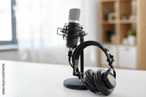 Canvas Print technology and audio equipment concept - headphones and microphone at home offic