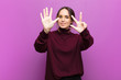 Leinwanddruck Bild - young pretty woman smiling and looking friendly, showing number eight or eighth with hand forward, counting down against purple wall