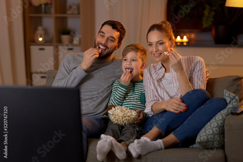 family, leisure and people concept - happy smiling father, mother and little son eating popcorn and watching tv at home in evening