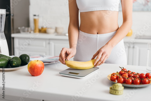 Selective focus of fit sportswoman putting banana on scales near measuring tape and notebook on table, calorie counting diet