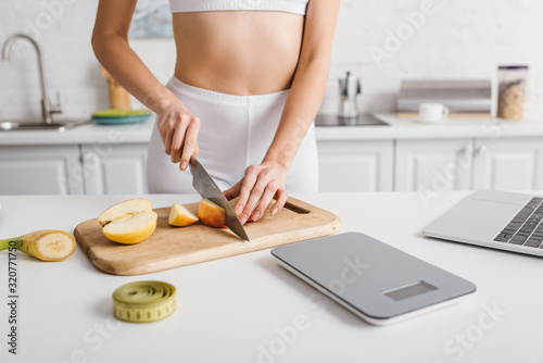 Cropped view of sportswoman cutting fruits near laptop, scales and measuring tape on kitchen table, calorie counting diet