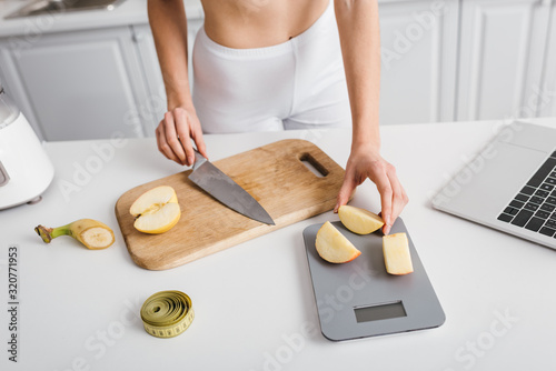 Cropped view of slim girl cutting fresh fruits near scales, measuring tape and laptop on kitchen table, calorie counting diet