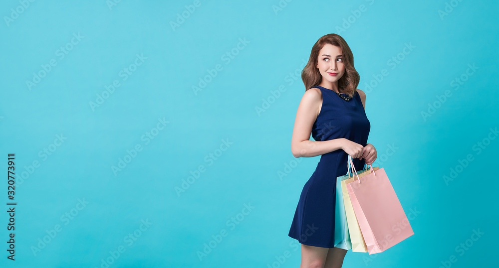 Fototapeta Happy beautiful young woman in blue dress and hand holding shopping bag at copy space isolated over blue background.