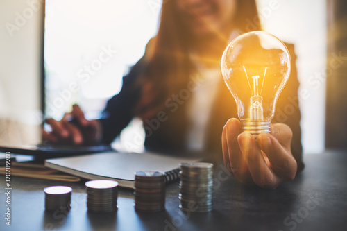 Businesswoman holding a lightbulb with coins stack on table, saving energy and m фототапет