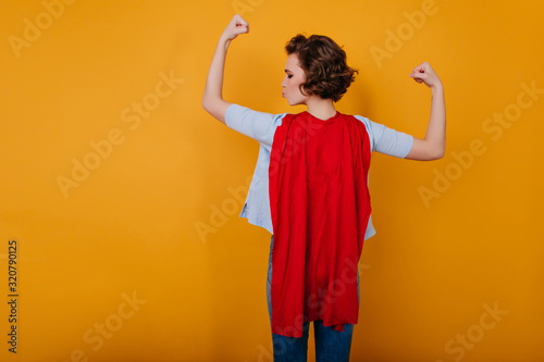 Funny wonderwoman looking at her muscles Slika na platnu