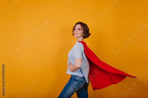 Photographie Smiling supergirl in jeans standing in confident pose on yellow background