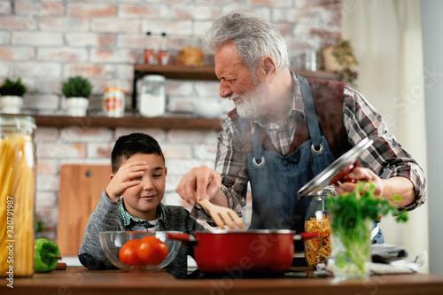 Fototapeta Grandpa and grandson in kitchen. Grandfather and his grandchild having fun while cooking. obraz