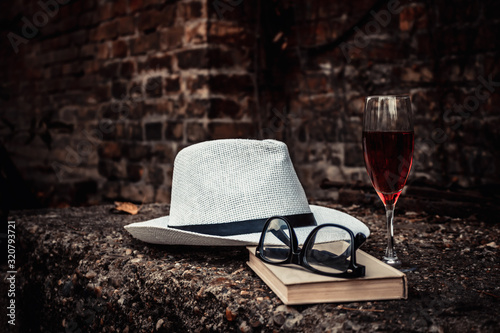 Fototapeta White hat with book and glass of red wine. obraz