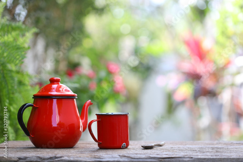 Fototapeta Red metal teapot with red tea cup on old wooden table front view  obraz