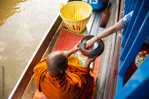 Thai people praying put food and thing offerings to monks procession on boat in Wallpaper Mural