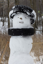 Snowman Decorated By Cars Tires Instead Of Hat And Scarf