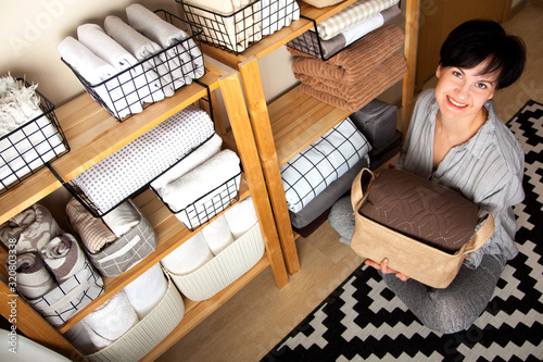 Fototapeta A woman is doing spring cleaning. Folds bedding, blankets, towels and duvet covers in a closet. The concept of housework and storage. obraz