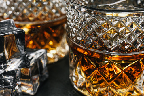 Photo two expensive glasses of whiskey with ice on a black stone tray