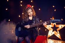 Portrait Of A Beautiful Rock Girl With Curly Hair Wearing Leather Jacket, Boots Playing The Electric Guitar While Sitting On A Red Tank In Recording Studio.