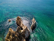 Aerial Shot From Above Of Blue Water Of White Rocky Cliffs And Sand Of The Shoreline Of Algarve, Portugal.