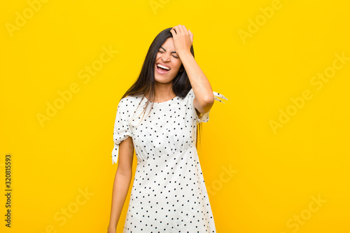 young pretty latin woman laughing and slapping forehead like saying d'oh! I fo Wallpaper Mural