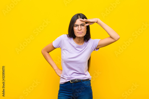 young pretty latin woman looking bewildered and astonished, with hand over foreh Wallpaper Mural