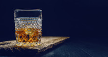 Glass Of Whiskey With Ice On A...