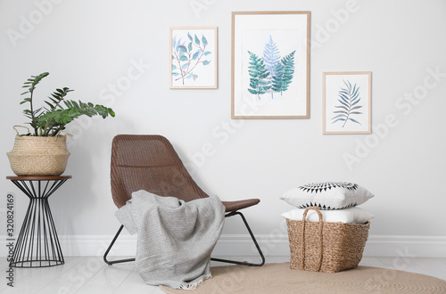 Fotografie, Obraz Comfortable armchair and plant near white wall indoors at home
