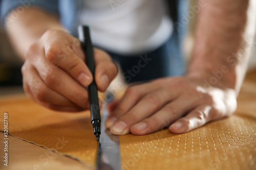 Fototapeta Man working with piece of leather in workshop, closeup obraz