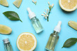Leinwanddruck Bild Flat lay composition with bottles of citrus essential oil on light blue background