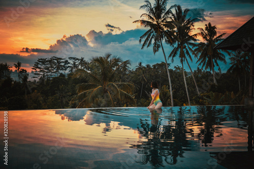 Woman relaxes in a luxury infinity pool overlooking the jungle at sunset in Ubud, Bali. A girl sits on the edge of the infinity pool against the backdrop of a bright beautiful sunset and the jungle.