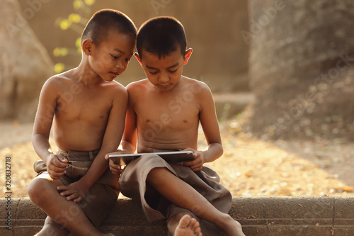 Two Asian boys are interested in learning different things on their tablets Fototapete