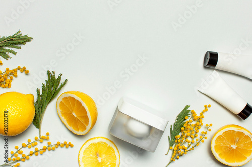 Cuadros en Lienzo White cosmetic bottle containers with yellow Mimosa flowers and fresh lemon on gray background top view flat lay