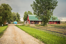 Typical American Rural Farm House Painted Red With Green Roof. Laurel, Montana, USA
