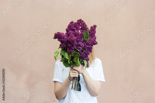 Canvas-taulu Woman holding a vivid bunch of lilac flowers against brick wall