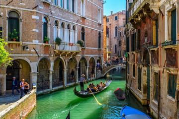 Narrow canal with gondola and bridge in Venice, Italy. Architecture and landmark of Venice. Cozy cityscape of Venice.