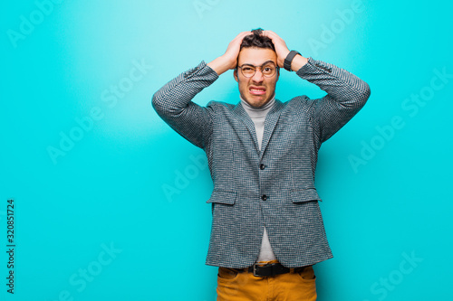 young arabian man feeling frustrated and annoyed, sick and tired of failure, fed-up with dull, boring tasks against blue wall
